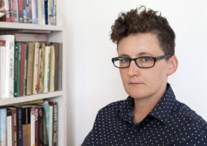 Mo Moulton (white person with glasses and short curly hair) sits next to a bookcase.